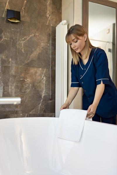 chambermaid placing towel on bathtub while