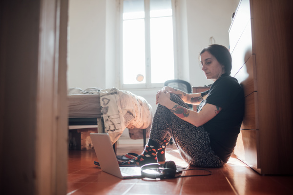 woman sitting on bedroom floor with