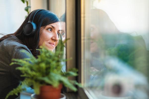woman wearing headphones looking through window