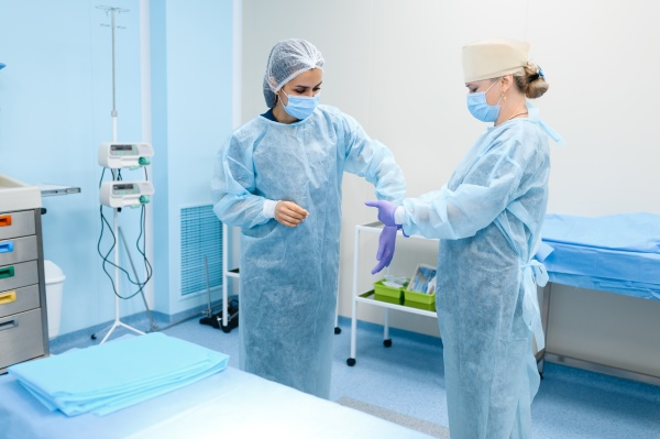female surgeon and assistant puts on