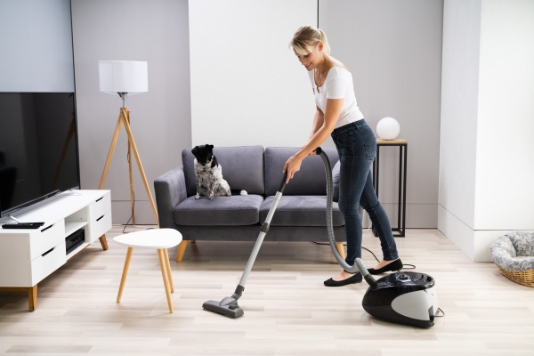 young maid cleaning carpet with vacuum