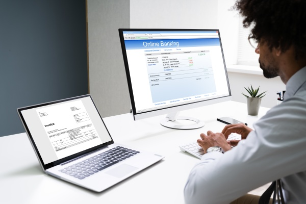 young businessman looking at invoice while