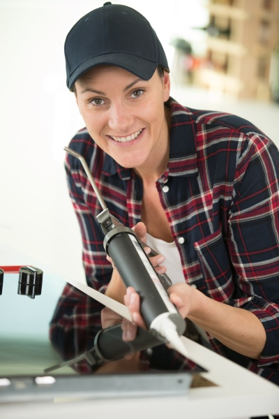 woman using silicone for gluing kitchen