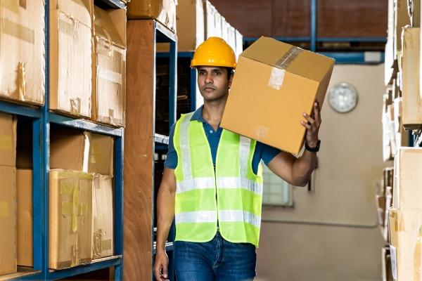 indian warehouse worker hold cardboard box