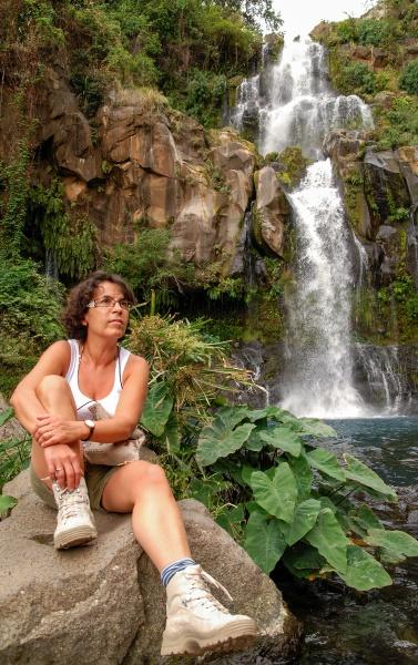 female hiker near wild splashing waterfall