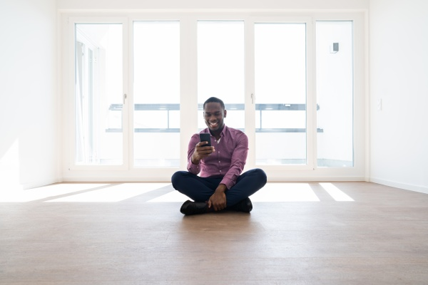 african man sitting in empty house