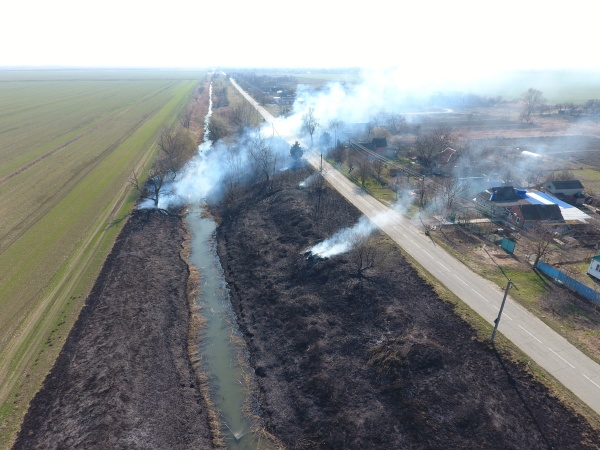burning dry grass along the irrigation