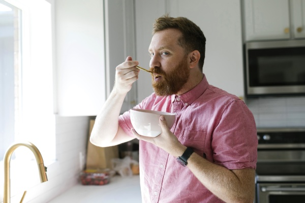 man eating cereal breakfast in kitchen