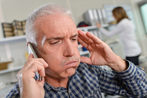man on telephone looking stressed