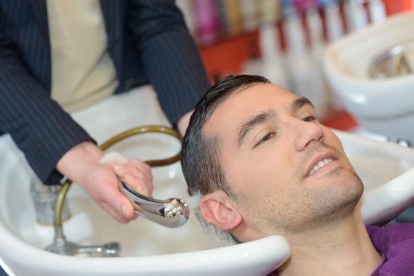 female hairdresser washing handsome clients hair