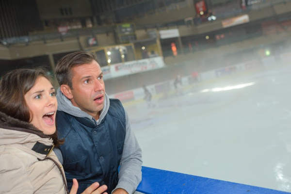 anxious couple watching game on ice