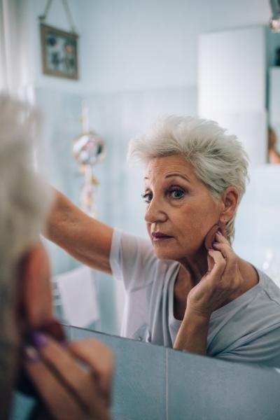 senior woman looking in mirror applying