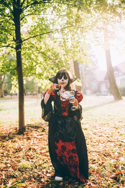 girl in halloween costume blowing