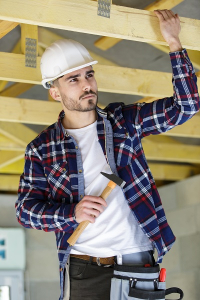 male builder on the roof of