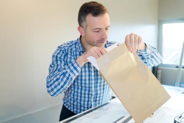 positive businessman opening an envelop