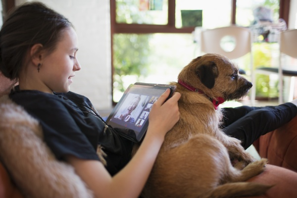 girl with dog video chatting with
