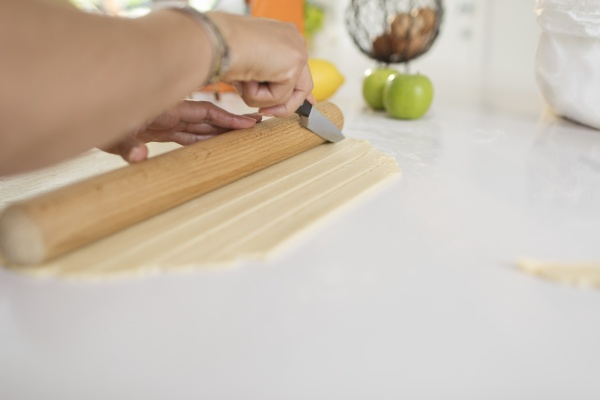 woman slicing pie dough with knife