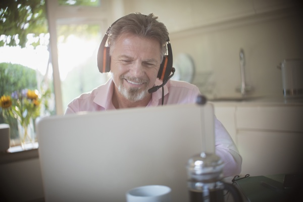 happy senior man with headphones working
