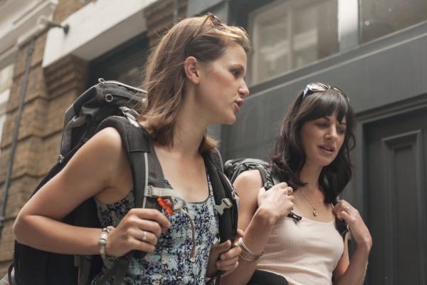 beautiful female backpackers talking while walking
