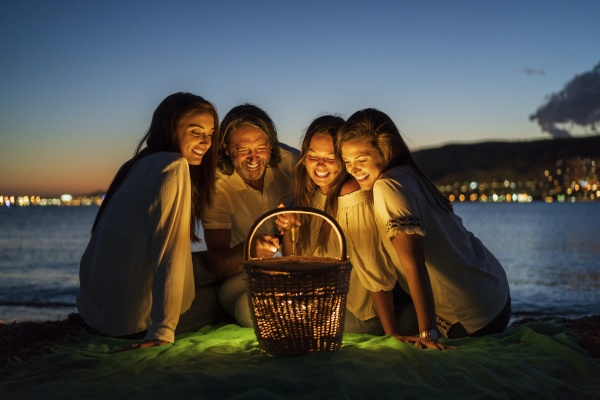 man with daughters looking at illuminated