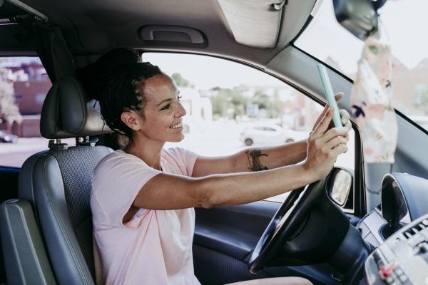 smiling woman taking selfie while sitting