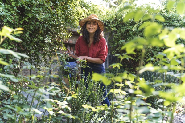 mature woman wearing hat watering trees