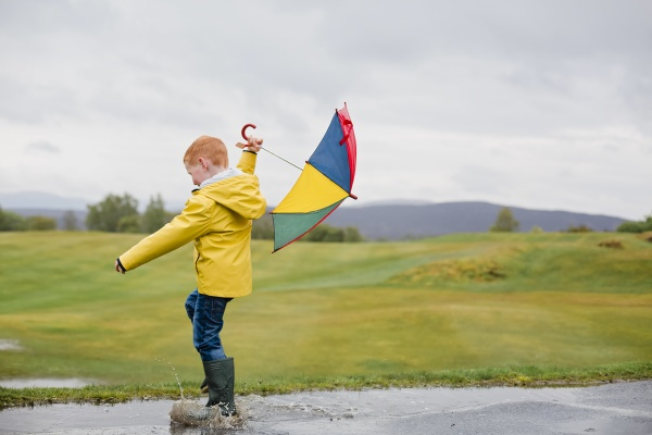redheaded little boy with umbrella playing
