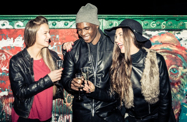 friends holding champagne glasses standing at