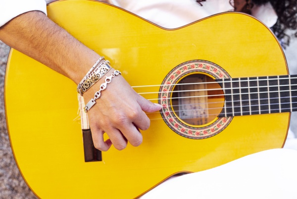 guitarist hand playing guitar while sitting