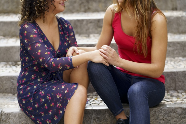 lesbian couple holding hands while sitting