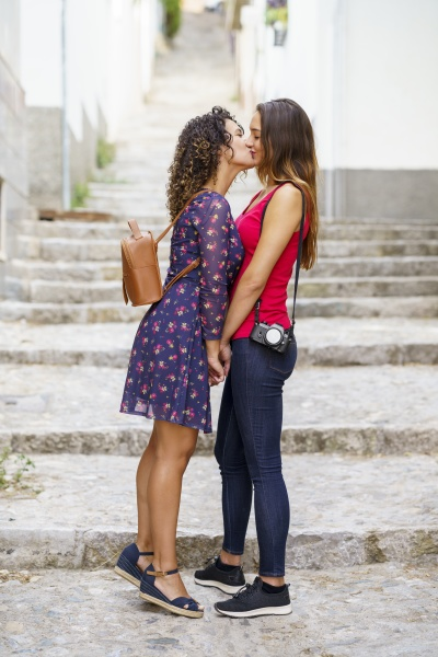lesbian couple kissing while standing against