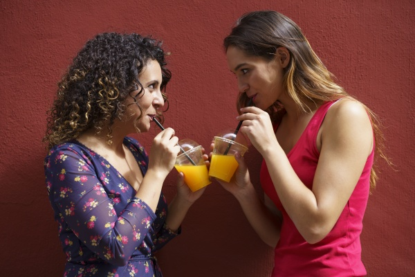 female couple drinking juice while standing