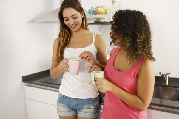 lesbian couple drinking coffee while standing