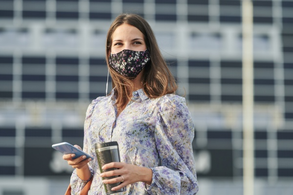 young woman wearing face mask using