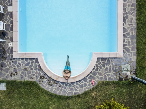drone view of man relaxing swimming
