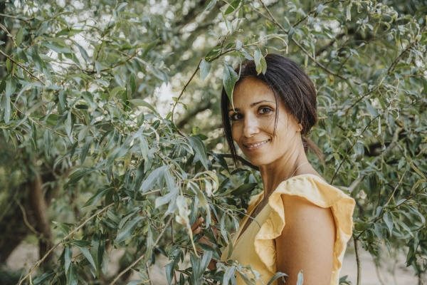 mature woman standing under willow tree