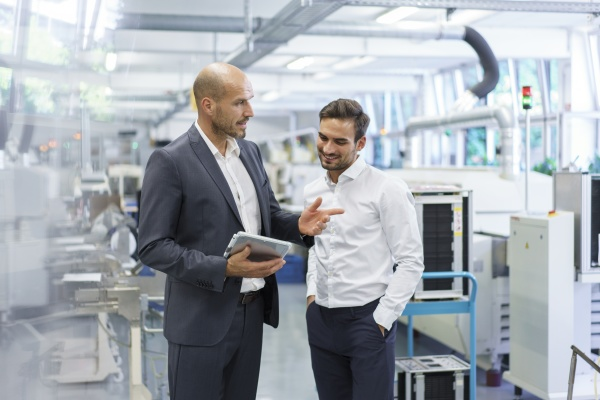 confident businessman discussing with engineer over