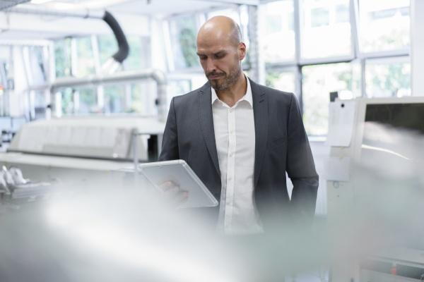balding businessman looking at digital tablet