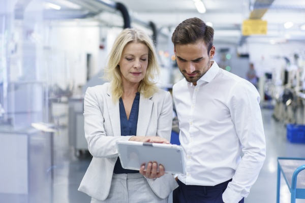 confident blond businesswoman discussing over digital