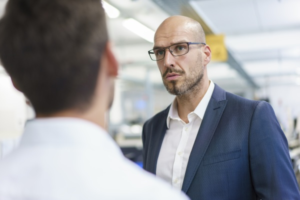 confident bald businessman looking at young