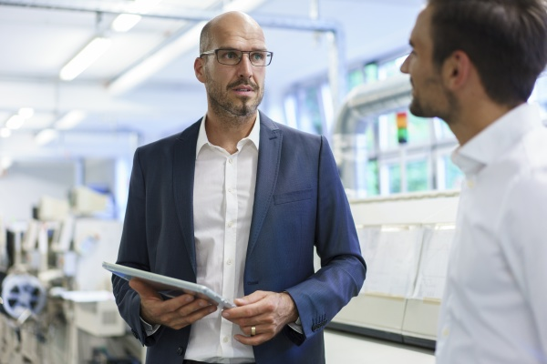 confident businessman holding digital tablet discussing