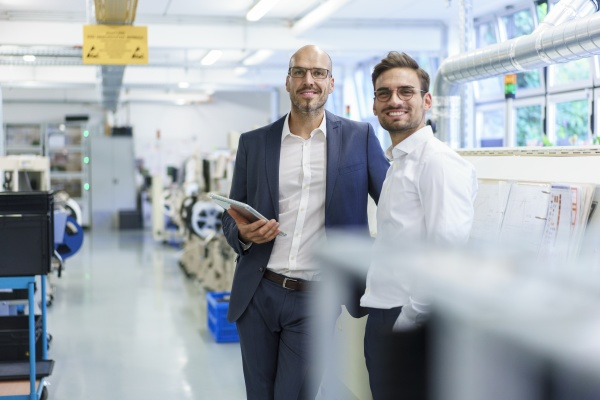 smiling male colleagues standing by machinery