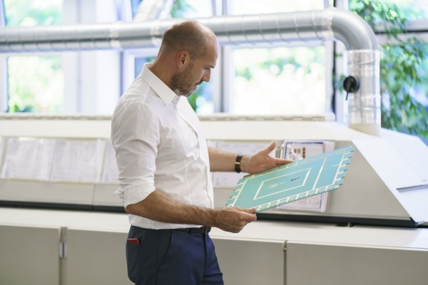 confident mature male engineer examining large