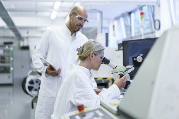 male technician standing by female scientist