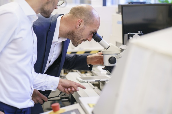 young technician pointing to male colleague