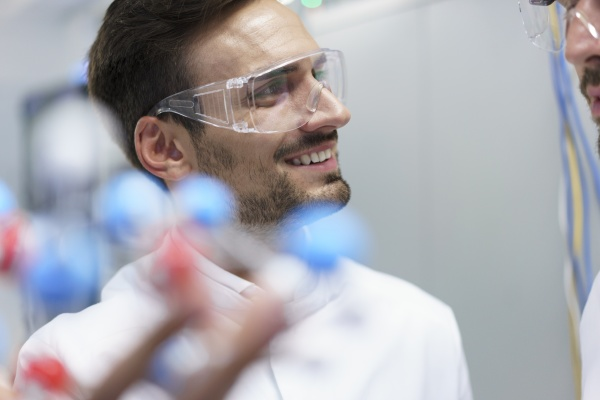 smiling male scientist holding molecular structure