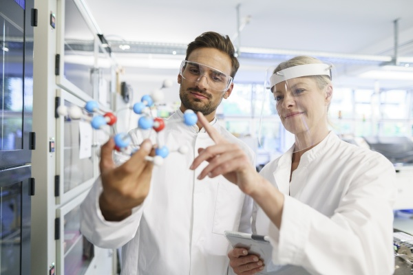 smiling female scientist touching molecular structure