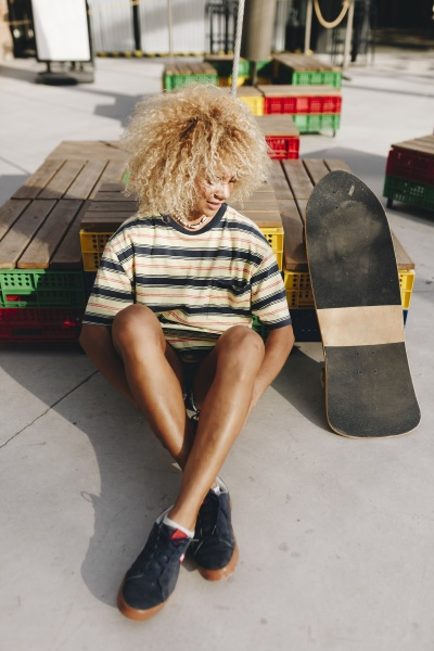 afro blond woman sitting by skateboard
