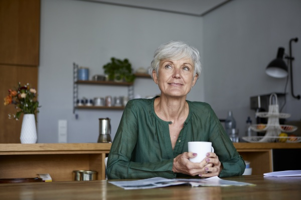 thoughtful senior woman sitting with coffee