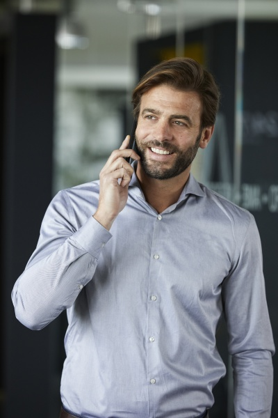 businessman smiling while talking on mobile